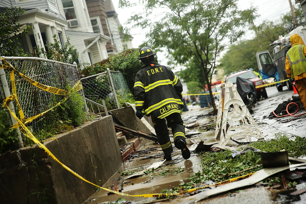 . Firefighters work at the scene of a five-alarm fire that burned for several hours on June 5, 2014 in the Staten Island borough of New York City. The fire at three townhouses on Staten Island started at around 1am and injured 23 firefighters and 11 civilians. It took 200 firefighters to control the blaze.  (Photo by Spencer Platt/Getty Images)