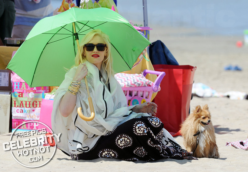 Spot The Rock Star! Beach-goers Couldn't Miss Gwen Stefani On The Beach Holding A Bright Green Parasol!