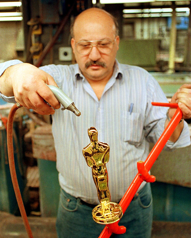 . Nunzio Giganti uses a compressed air sprayer to dry an Oscar statuette after pulling it from a gold-plating solution at R.S. Owens in Chicago, Illinois, 02 February. The statuettes are cast, polished and plated with copper, nickel, silver and then gold in preparation for the upcoming Academy Awards to be presented in Los Angeles 21 March.   JOHN ZICH/AFP/Getty Images