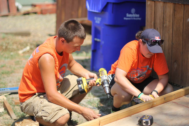 Fuller Center Bicycle Adventurers take a break from their summer ride to help build a ramp at a home.
