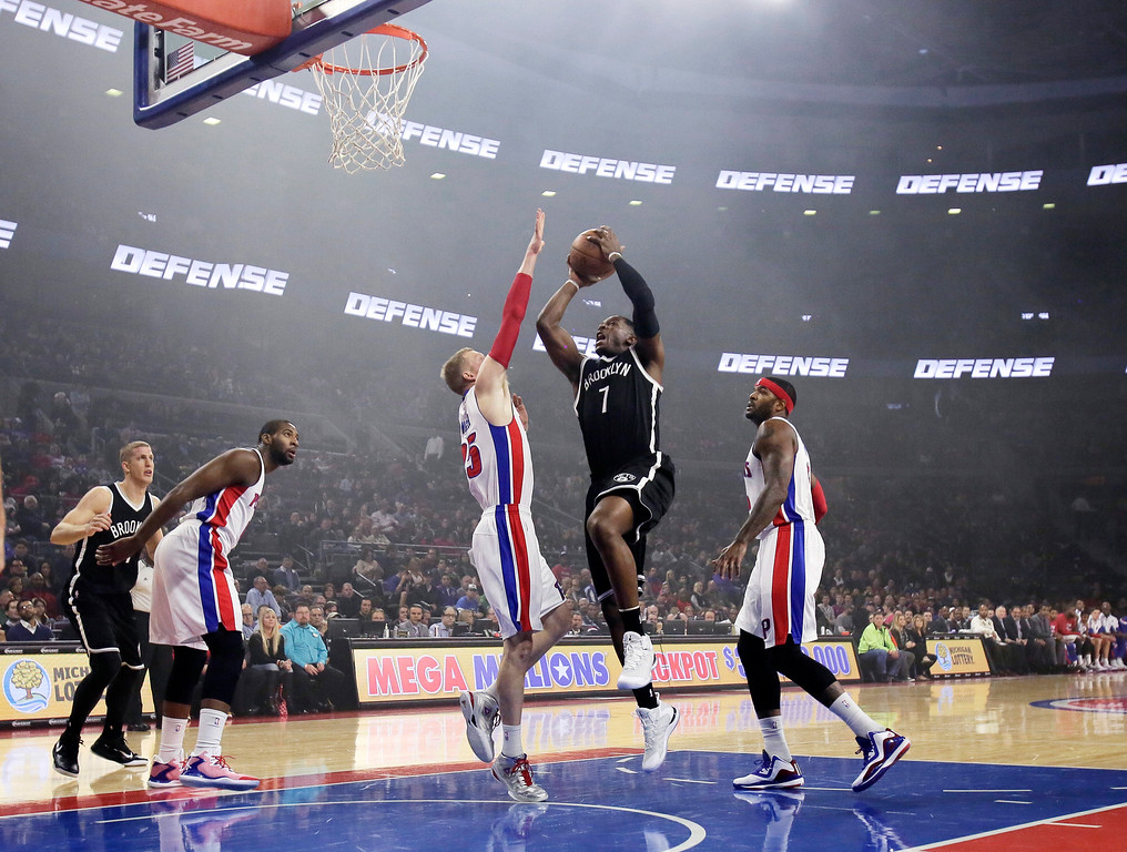 . Brookyn Nets\' Joe Johnson (7) takes a shot against Detroit Pistons\' Kyle Singler (25) with theatrical smoke still in the arena at the start of an NBA basketball game Saturday, Nov. 1, 2014, in Auburn Hills, Mich. (AP Photo/Duane Burleson)