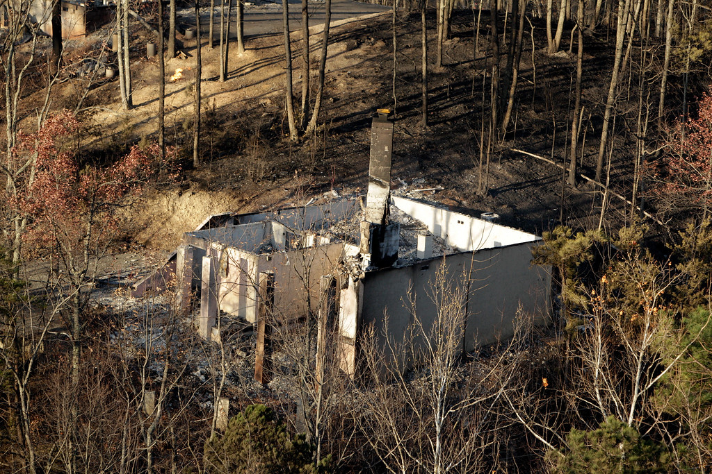 . An aerial photo shows a home and trees burned by a wildfire Tuesday, Nov. 29, 2016, near Gatlinburg, Tenn. Thousands of people have fled wildfires that killed at least three people and destroyed hundreds of homes and a resort in the Great Smoky Mountains. (AP Photo/Wade Payne)