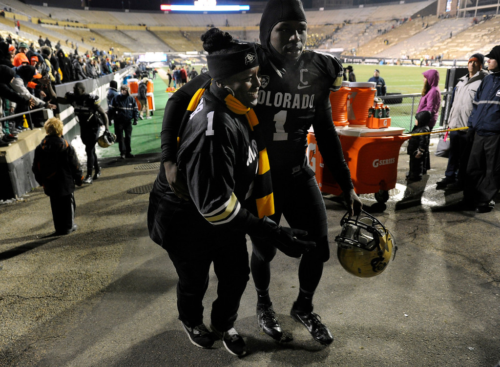 . BOULDER, CO - NOVEMBER 23: After braving hours of freezing temperatures, Felicia Morris, left, the mother senior Derrick Webb, a linebacker for the Colorado Buffaloes football team, runs on to Folsom Field to greet her son at the end of the game against the Southern California Trojans at Folsom Field in mid-November. It is senior day and the last home game of the season, and each senior player is recognized and greeted by family and friends on the field. (Photo by Kathryn Scott Osler/The Denver Post)