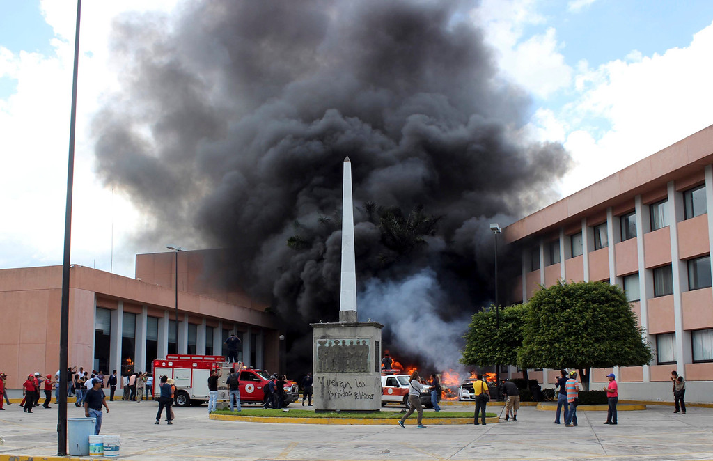 . Firefighters arrive to try to extinguish several burning vehicles in front of the state congress building after protesting teachers torched them in the state capital city of Chilpancingo, Mexico, Wednesday Nov. 12, 2014.  (AP Photo/Alejandrino Gonzalez)