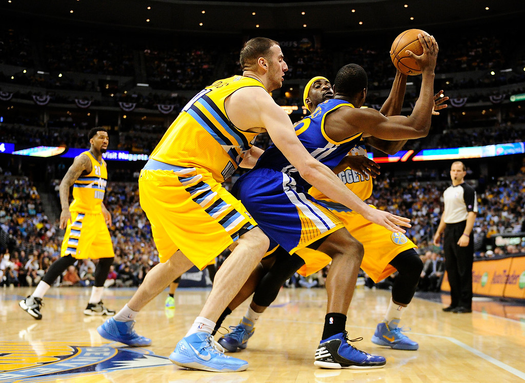 . DENVER, CO. - APRIL 23: Golden State Warriors small forward Harrison Barnes (40) is tightly guarded by Denver Nuggets center Kosta Koufos (41) and Denver Nuggets point guard Ty Lawson (3) in the second quarter. The Denver Nuggets took on the Golden State Warriors in Game 2 of the Western Conference First Round Series at the Pepsi Center in Denver, Colo. on April 23, 2013. (Photo by AAron Ontiveroz/The Denver Post)