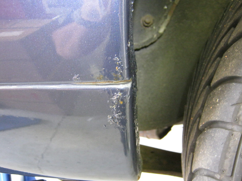 Rust in sill end and wheel arch, left rear