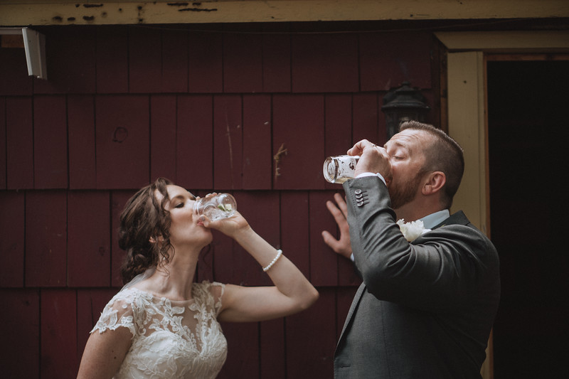 The bride and groom chug their beers outside on the bar patio.