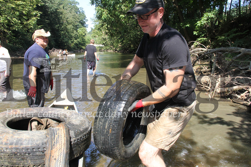 Dean Catalana, left, and Robert Green pull a tire out of the Connoquenessing Creek Saturday during a cleanup event.