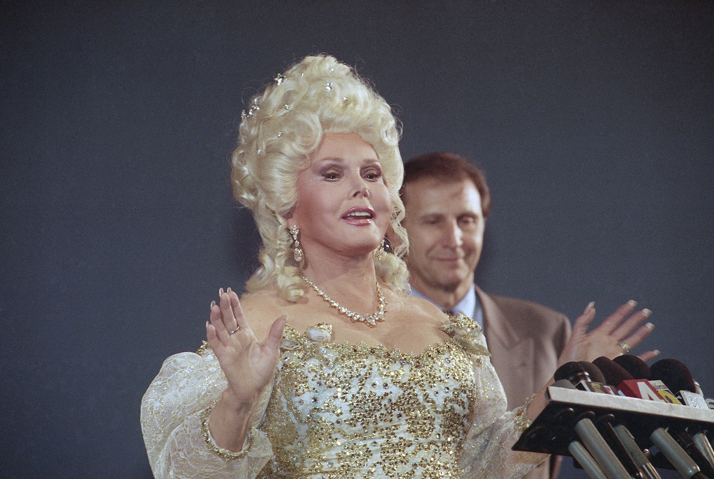 ". Actress Zsa Zsa Gabor responds to reporters questions during a news conference prior to a performance in the stage play ""Cinderella\""  on Wednesday, Dec. 8, 1993, in Los Angeles, as her attorney Neil C. Newson looks on.    A jury ordered Gabor and her husband to pay actress Elke Sommer another $1.2 million for allegedly telling German publications the actress is a Hollywood has-been. (AP Photo/Chris Martinez)"