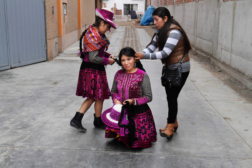 . Dancer Matilde Campo, center, is helped with her hair by members of her folkloric dance group before the beginning of Takanakuy ritual fighting in Lima, Peru. The Andean fight known as Takanakuy are preceding with traditional dancing and music. (AP Photo/Karel Navarro)