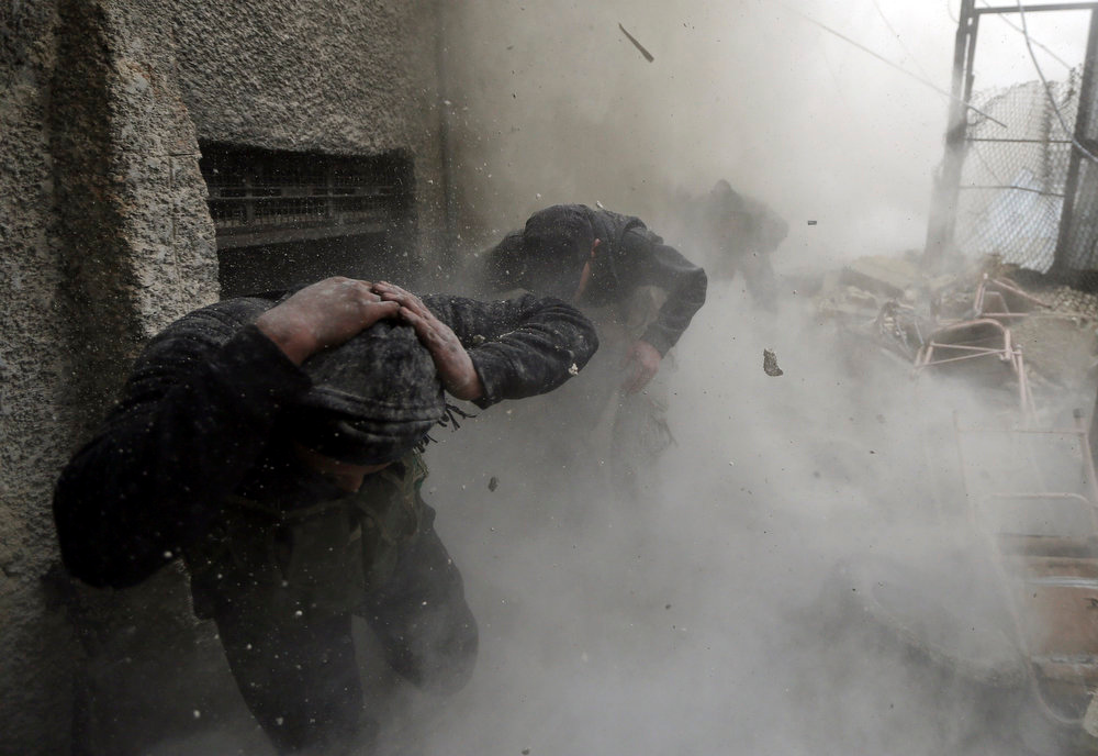 . Free Syrian Army fighters run for cover as a tank shell explodes on a wall during heavy fighting in the Ain Tarma neighborhood of Damascus January 30, 2013.  REUTERS/Goran Tomasevic