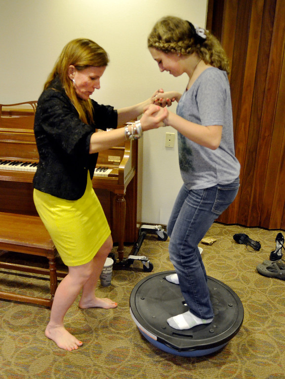 . Jeff Forman/JForman@News-Herald.com Heidi Skok helps Michaela Quick stand on a Bosu ball to do a breathing exercise during a voice lesson April 14 at the Willoughby Fine Arts Association.