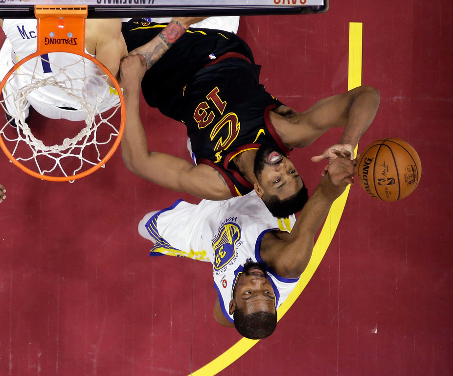 . Cleveland Cavaliers\' Tristan Thompson (13) and Golden State Warriors\' Kevin Durant reach for a rebound during the first half of Game 4 of basketball\'s NBA Finals, Friday, June 8, 2018, in Cleveland. (AP Photo/Carlos Osorio, Pool)