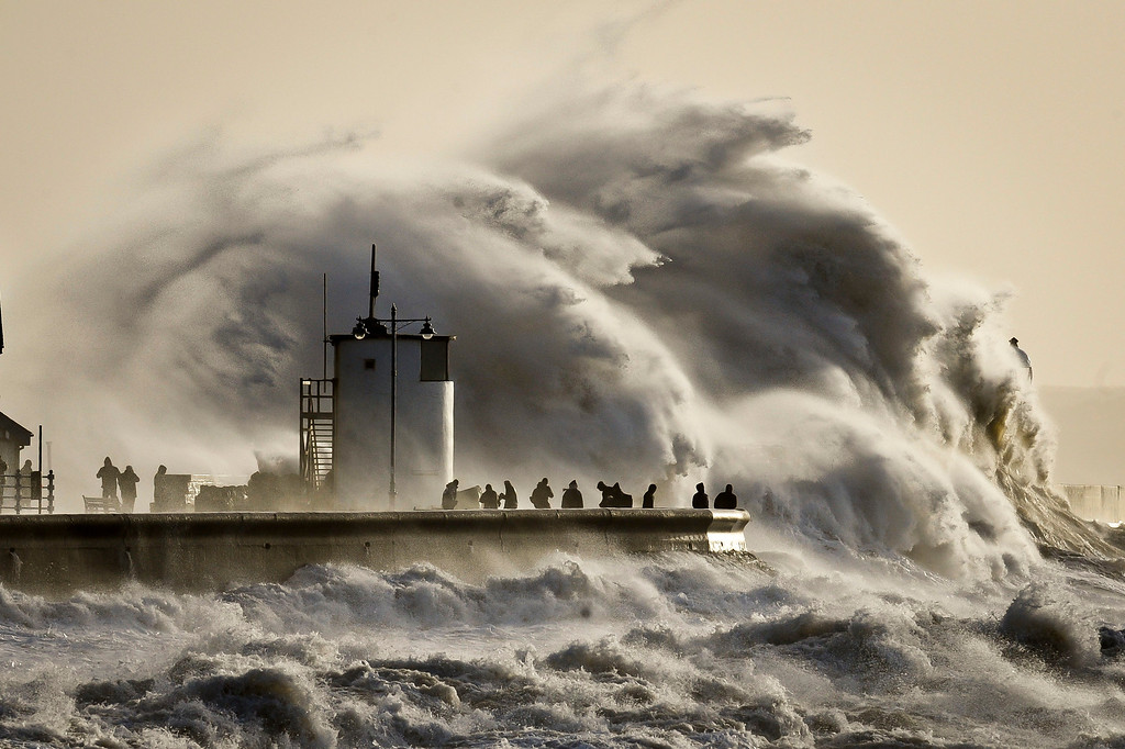 . People watch and photograph enormous waves as they break, on Porthcawl harbour, South Wales, Monday Jan. 6, 2014.  Residents along Britain\'s coasts are braced for more flooding as strong winds, rain and high tides lash the country. At least three people have died in a wave of stormy weather that has battered Britain since last week, including a man killed when his mobility scooter fell into a river in Oxford, southern England.  (AP Photo/PA, Ben Birchall)