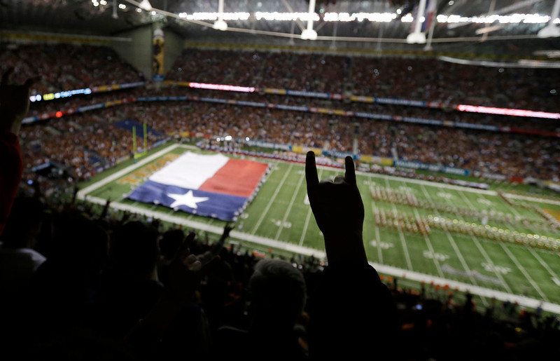 . A Texas fans holds up the hook\'em horns sign as the Texas band and Texas flag take the field prior to the Alamo Bowl NCAA football game between Texas and Oregon State, Saturday, Dec. 29, 2012, in San Antonio.  (AP Photo/Eric Gay)