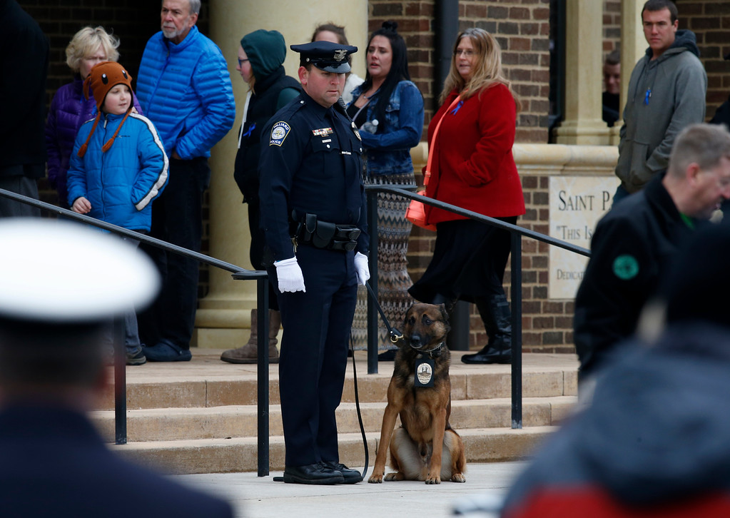 . A Hilliard, Ohio, K-9 unit stands outside St. Paul the Apostle Catholic Church in Westerville, Ohio, before funeral services for Westerville police officers Anthony Morelli and Eric Joering Friday, Feb. 16, 2018. The two veteran officers were shot after entering a residence Saturday.  The officers returned fire, wounding 30-year-old Quentin Smith, who has been charged with aggravated murder and remains hospitalized. (AP Photo/Paul Vernon)