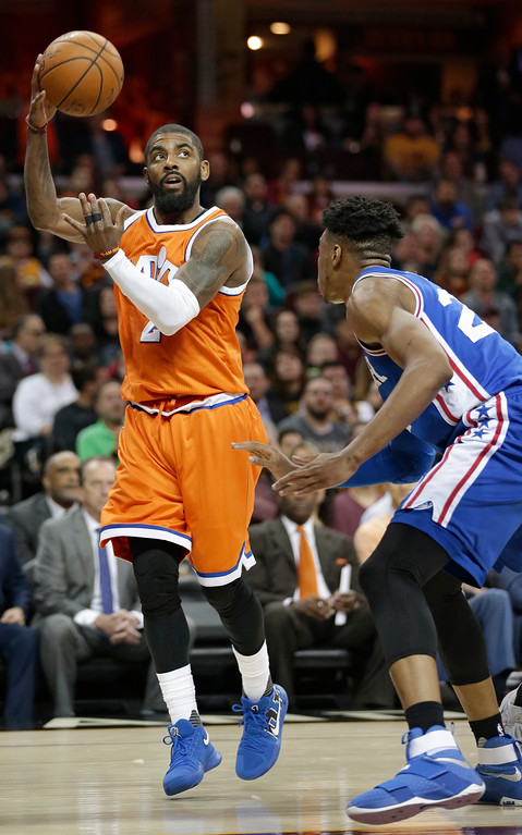 . Cleveland Cavaliers\' Kyrie Irving, left, passes over Philadelphia 76ers\' Richaun Holmes in the first half of an NBA basketball game, Friday, March 31, 2017, in Cleveland. (AP Photo/Tony Dejak)