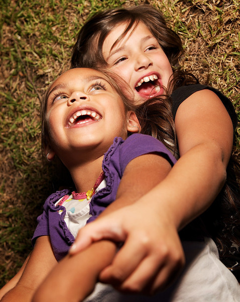 Aboriginal Girl laughing with Caucasian Girl on ground