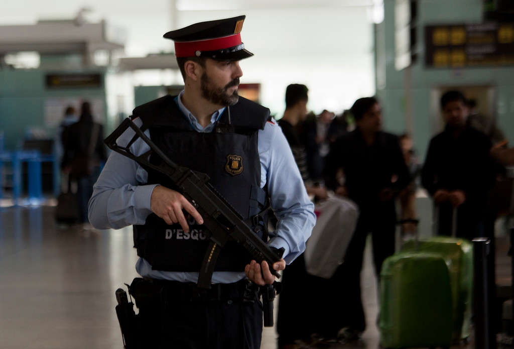 . A police officer guards a terminal of the airport during tighter security measures  in Barcelona, Spain, Tuesday, March 22, 2016. Explosions, at least one likely caused by a suicide bomber, rocked the Brussels airport and subway system Tuesday, prompting a lockdown of the Belgian capital and heightened security across Europe. (AP Photo/Emilio Morenatti)