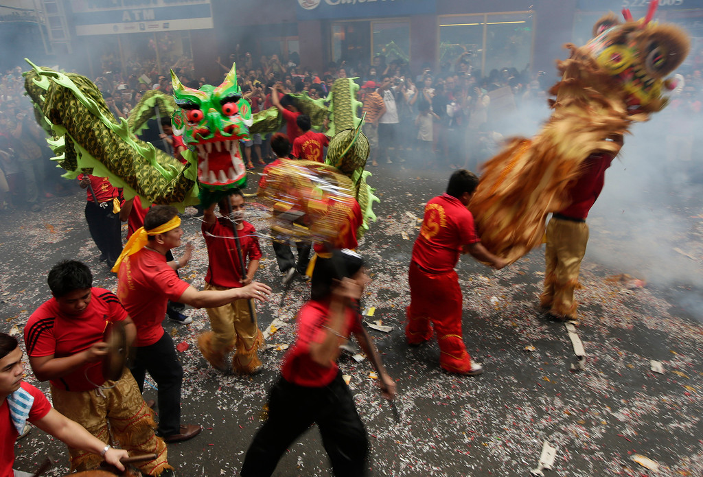 . Firecrackers explode as dragon and lion dancers perform in front of a grocery store in celebration of Chinese New Year at Manila\'s Chinatown district of Binondo, Philippines Friday, Jan. 31, 2014.  (AP Photo/Bullit Marquez)