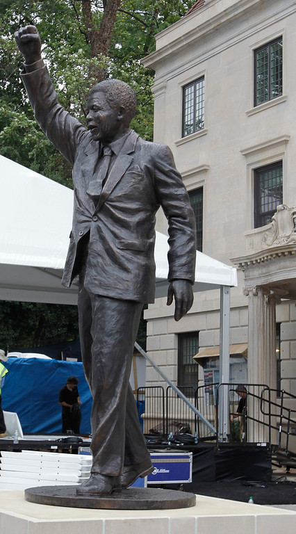 . A statue of former South African President Nelson Mandela stands outside the newly-renovated South African embassy in Washington after its unveiling on Saturday, Sept. 21, 2013. The 9-foot statue was made by Cape Town sculptor Jean Doyle. (AP Photo/Luis M. Alvarez)