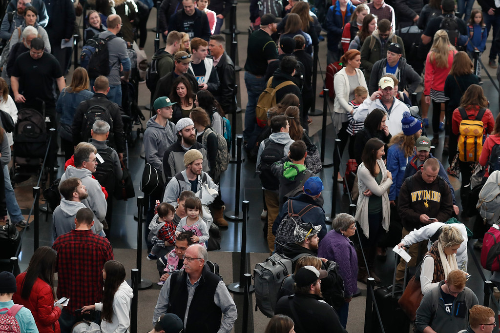 . Travelers queue up in at a security checkpoint at Denver International Airport early Wednesday, Nov. 23, 2016, in Denver. Travelers are criss-crossing the country Wednesday, clogging airport terminals in a rush to reach their Thanksgiving Day destinations. (AP Photo/David Zalubowski)