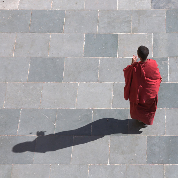 Young monk flipping a coin (see the shadow) at Thiksey Monastery (also called a gompa or gonpa).  Ladakh, India