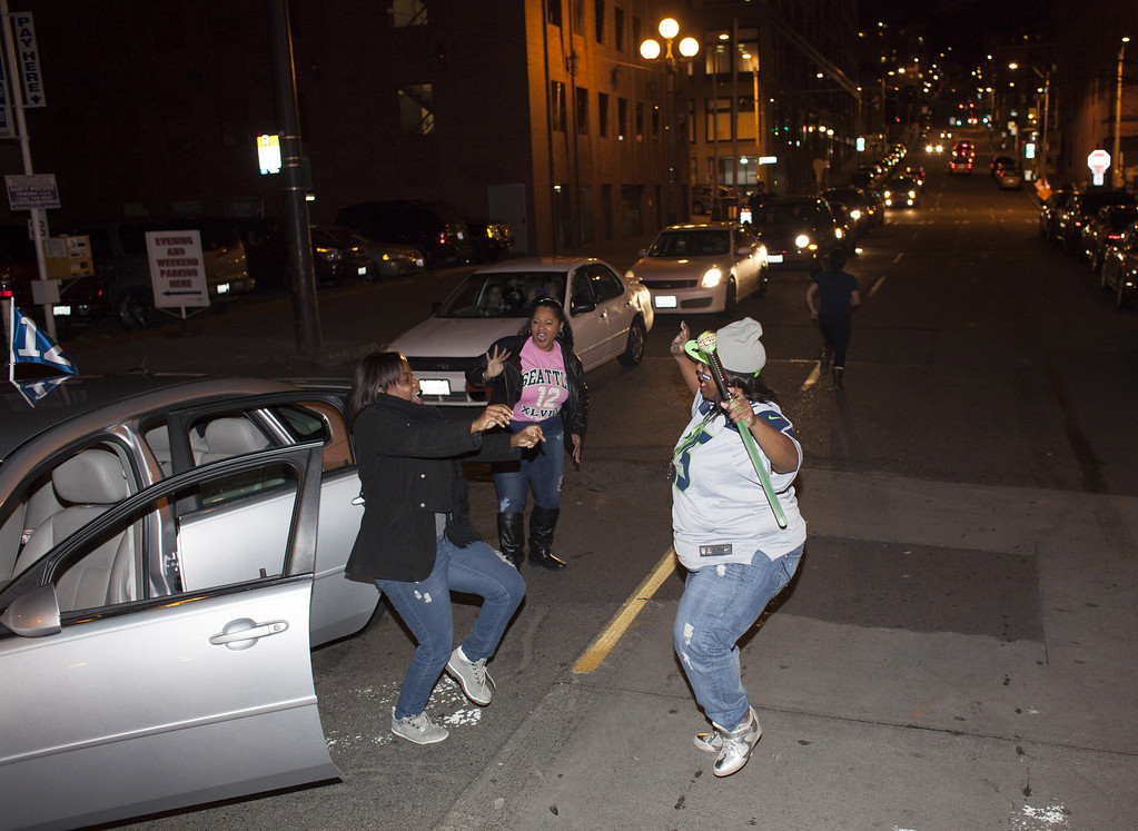 . Seattle Seahawks fans jump out of their car and dance in the street after watching their team win the Super Bowl on February 2, 2014 in Seattle, Washington. The Seahawks defeated the Denver Broncos 43-8 in Super Bowl XLVIII.  (Photo by David Ryder/Getty Images)