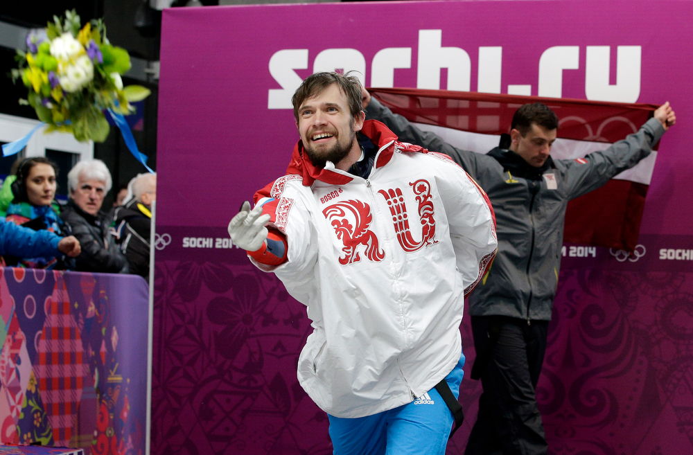 . Alexander Tretiakov of Russia tosses his flowers after the ceremony for winning the gold medal in the men\'s skeleton competition at the 2014 Winter Olympics, Saturday, Feb. 15, 2014, in Krasnaya Polyana, Russia. Walking behind him is silver medalist Martins Dukurs of Latvia. (AP Photo/Michael Sohn)