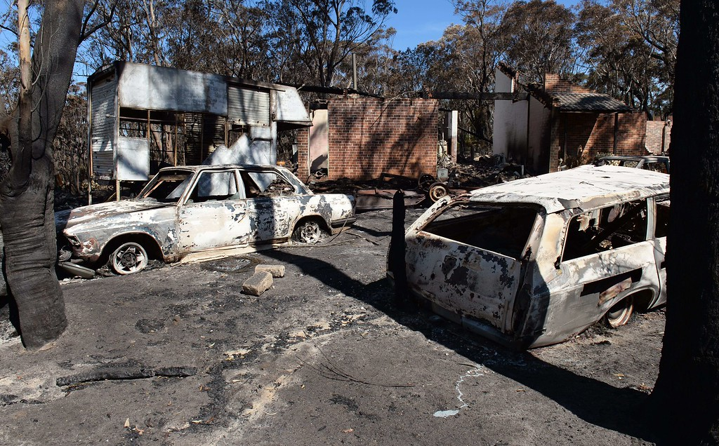""". Burnt out cars sit in front of a destroyed house at Mount Victoria in the Blue Mountains on October 21, 2013, as volunteer fire brigades race to tame an enormous blaze with officials warning it could merge with others to create a \""""mega-fire\"""" if weather conditions worsen.   AFP PHOTO/William WEST/AFP/Getty Images"""