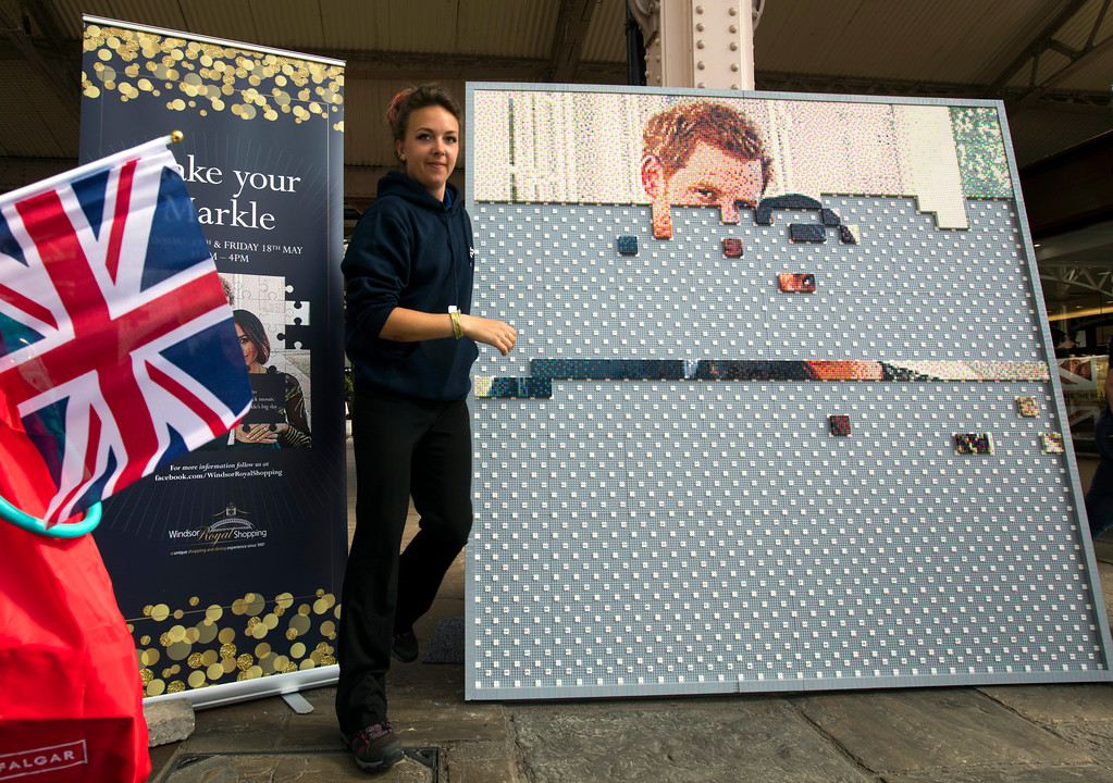 . A hostess walks past a mosaic of the royal couple in a shopping mall in Windsor, England, Friday, May 18, 2018. Preparations continue in Windsor ahead of the royal wedding of Britain\'s Prince Harry and Meghan Markle Saturday May 19. (AP Photo/Peter Dejong)