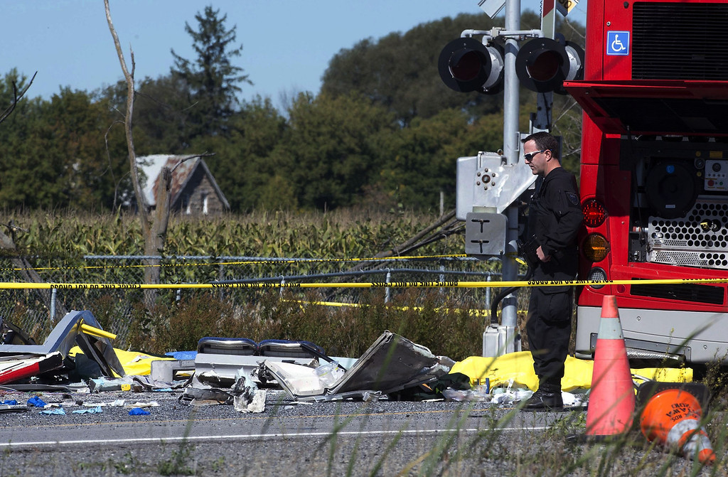 . A police officer surveys the debris from a collision between a city bus and Via Rail train, Wednesday Sept. 18, 2013 in Ottawa, Canada. Witnesses said the bus went through a closed crossing barrier. (AP Photo/The Canadian Press, Adrian Wyld)