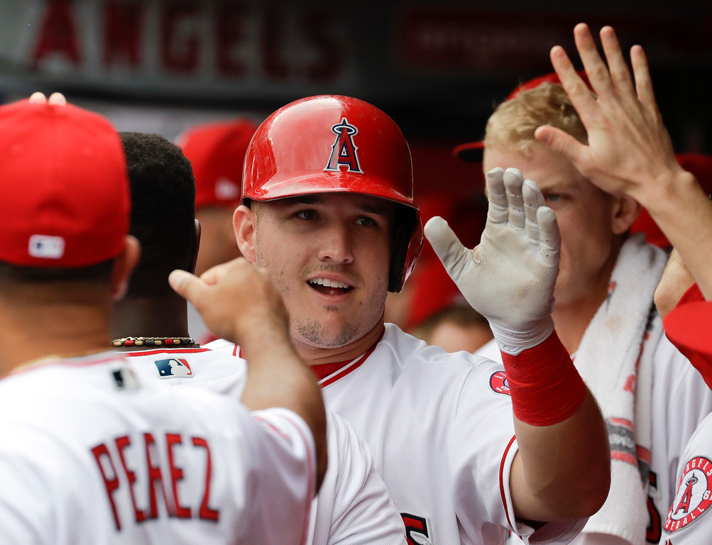 . Los Angeles Angels\' Mike Trout celebrates in the dugout after scoring on a double by Albert Pujols during the first inning of a baseball game against the Cleveland Indians in Anaheim, Calif., Thursday, Sept. 21, 2017. (AP Photo/Chris Carlson)