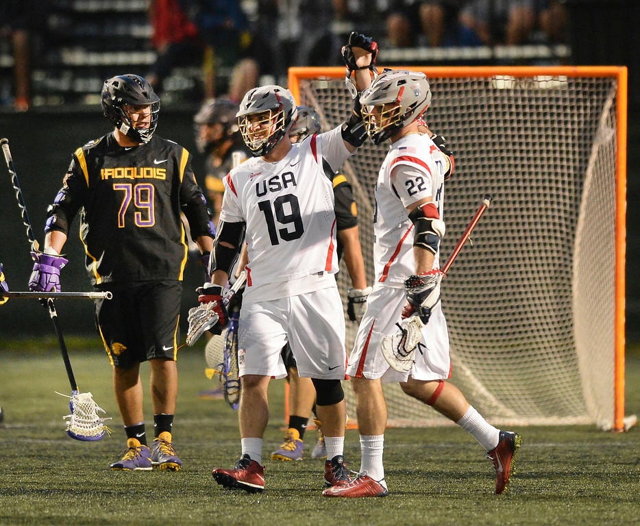 . United States attack Kevin Leveille (19) celebrated a goal with midfielder Ned Crotty (22) late in the fourth quarter. The United States defeated the Iroquois Nationals 18-5 Tuesday night, July 15, 2014.   Photo by Karl Gehring/The Denver Post