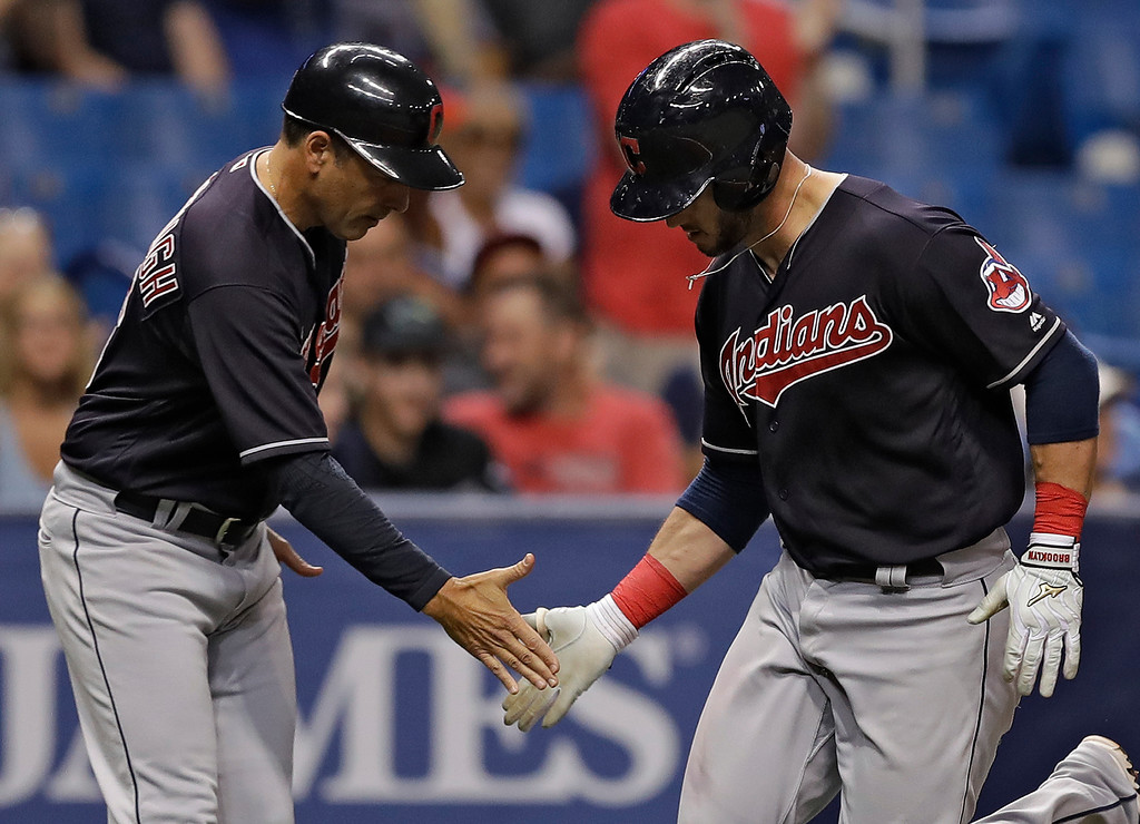 . Cleveland Indians\' Yan Gomes, right, shakes hands with third base coach Mike Sarbaugh after Gomes hit a home run off Tampa Bay Rays pitcher Tyler Glasnow during the fifth inning of a baseball game Tuesday, Sept. 11, 2018, in St. Petersburg, Fla. (AP Photo/Chris O\'Meara)