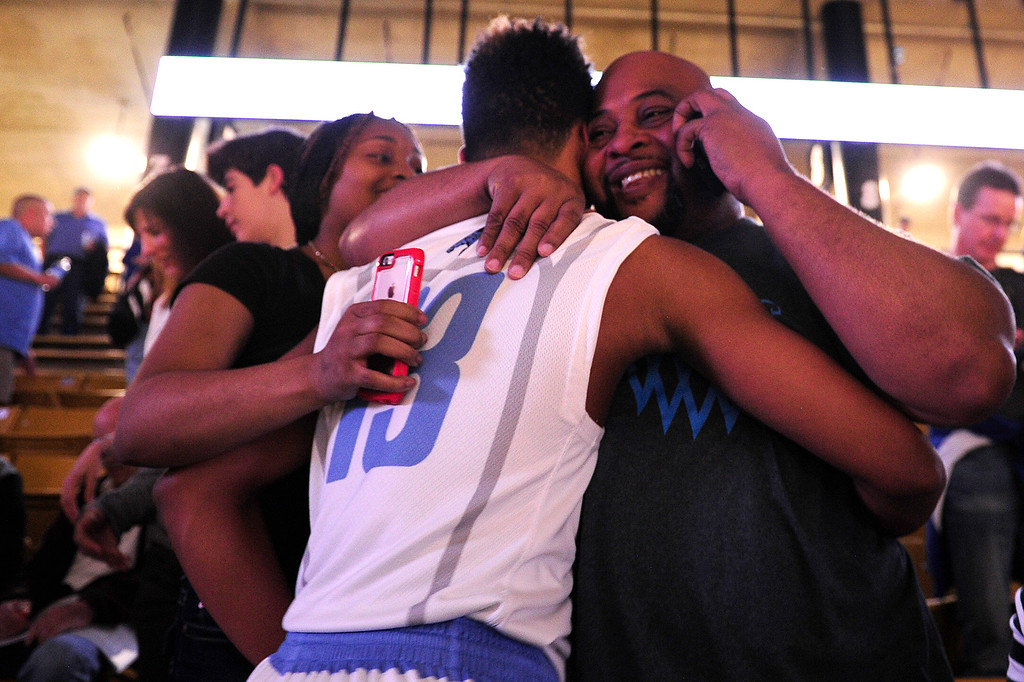 . Pierre Taylor (13) of Pueblo West hugs his father Pierre Taylor Sr. after defeating Vista Ridge to advance at the Coors Events Center on March 11, 2016 in Boulder, Colorado. Pueblo West defeated Vista Ridge 65-54 to advance to the 4A finals of Colorado state basketball tournament.  (Photo by Brent Lewis/The Denver Post)