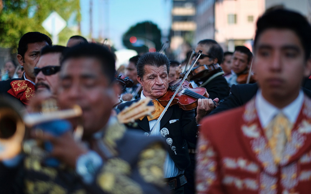 . Mariachis play on the street during the Santa Cecilia procession and festival in the Boyle Heights section of Los Angeles on Tuesday, Nov. 22, 2016. Musicians from around the country gathered for Mariachi Sol de Mexico to celebrate Santa Cecilia. The festival honors Santa Cecilia, the patron saint of musicians. (AP Photo/Richard Vogel)