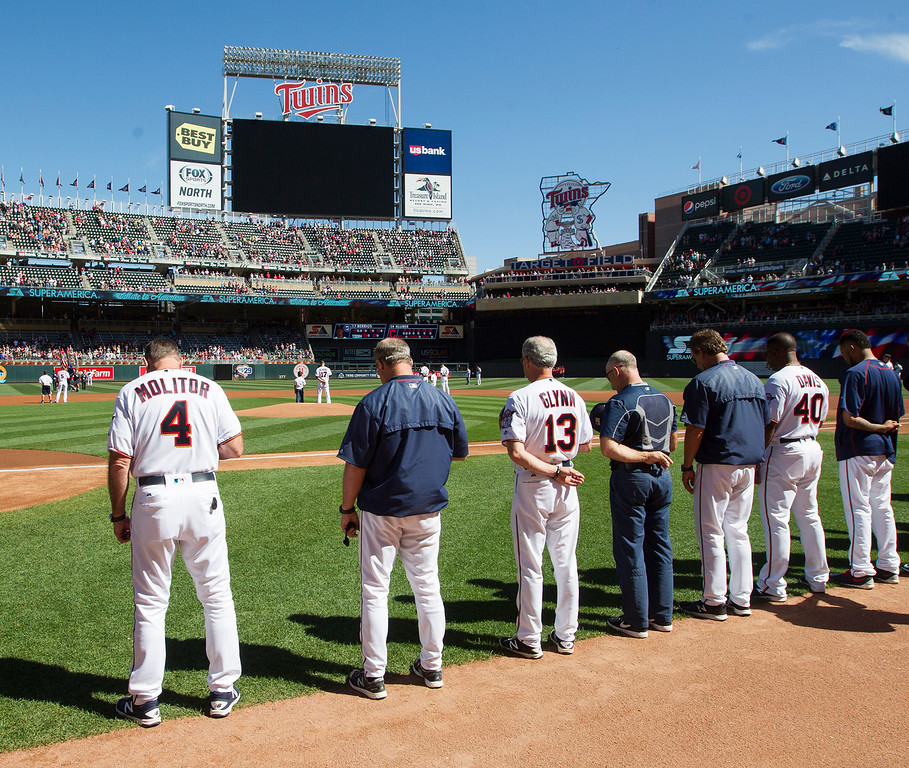 . The Minnesota Twins, including manager Paul Molitor (4), stand for a moment of silence in honor of September 11th before a baseball game against the Cleveland Indians, Sunday, Sept. 11, 2016, in Minneapolis. (AP Photo/Paul Battaglia)