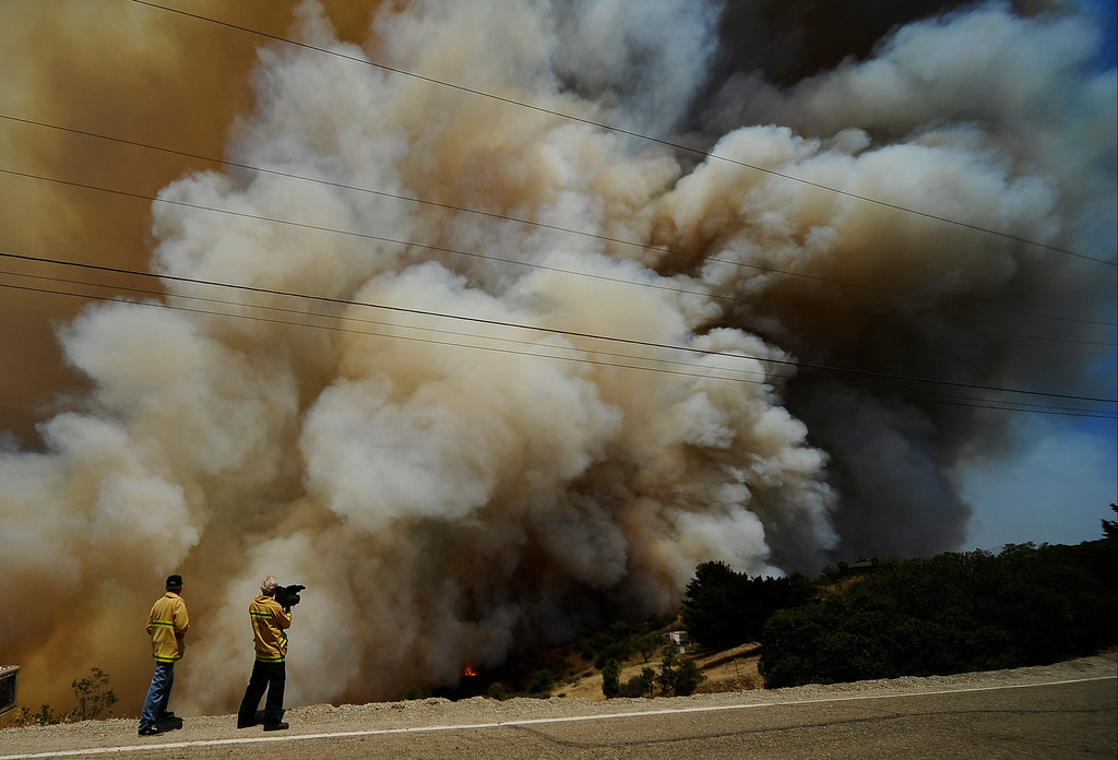 . Fire photographers get up close to huge blooms of smoke going up into the sky during the second day of the Springs Fire in the mountain areas of Ventura County CA.  May 3, 2013. A fierce, wind-whipped brush fire spread on Friday along the California coast northwest of Los Angeles, threatening several thousand homes and a military base as more than 1,100 dwellings were ordered evacuated and a university campus was closed. May 2,2013. Ventura County California.  Photo by Gene Blevins/LA Daily News