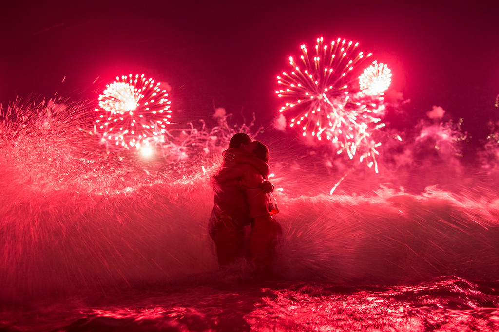 . A wave crashes on two girls hugging as they usher in the new year, while fireworks explode over Copacabana beach, during New Year celebrations in Rio de Janeiro, Brazil, Thursday, Jan. 1, 2015. (AP Photo/Felipe Dana)