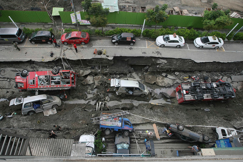 . Vehicles are left lie in a destroyed street following multiple explosions from an underground gas leak in Kaohsiung, Taiwan, early Friday, Aug. 1, 2014. A massive gas leakage early Friday caused five explosions that killed scores of people and injured over 200 in the southern Taiwan port city of Kaohsiung. (AP Photo)