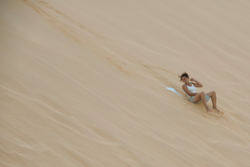 Woman sliding down the white sand dunes - Mui Ne, Vietnam