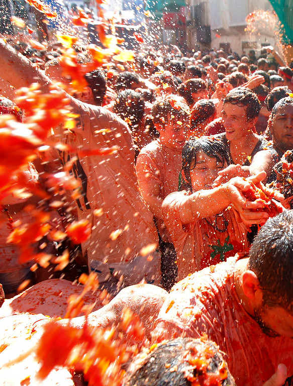 ". Crowds of people throw tomatoes at each other during the annual ""tomatina\"" tomato fight fiesta in the village of Bunol, 50 kilometers outside Valencia, Spain, Wednesday, Aug. 27, 2014. Thousands of people are splattering each other with tons of tomatoes in the annual \""Tomatina\"" battle. Bunol town says some 20,000 people are taking part in Wednesday\'s hour-long street bash, inspired by a food fight among kids back in 1945.  (AP Photo/Alberto Saiz)"