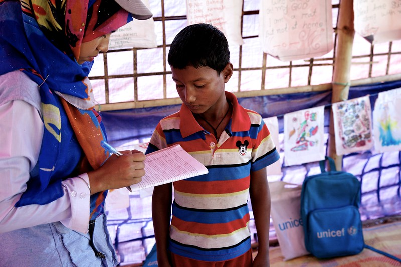 0120-0127Samira Akter, a Bangladeshi teacher, helps refugee students at a UNICEF-supported learning centre at the Balukhali makeshift settlement for Rohingya in Ukhia, Cox's Bazar, Bangladesh.     Photo: UNICEF / b.a.sujaN/Map