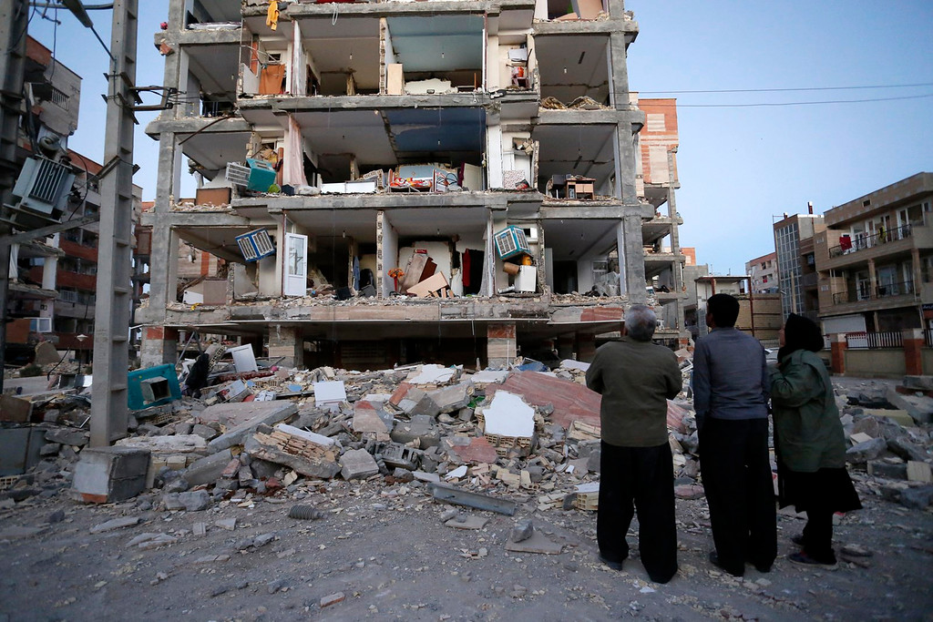 . In this photo provided by the Iranian Students News Agency, ISNA, people look at destroyed buildings after an earthquake at the city of Sarpol-e-Zahab in western Iran, Monday, Nov. 13, 2017. A powerful earthquake shook the Iran-Iraq border late Sunday, killing more than one hundred people and injuring some 800 in the mountainous region of Iran alone, state media there said. (Pouria Pakizeh/ISNA via AP)