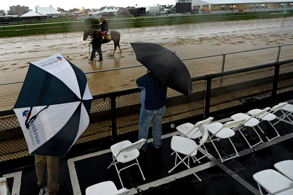 . As rain falls, exercise rider Willie Delgado takes Kentucky Derby winner California Chrome over the track in preparation for the 139th Preakness Stakes at Pimlico Race Course on May 16, 2014 in Baltimore, Maryland. (Photo by Patrick Smith/Getty Images)