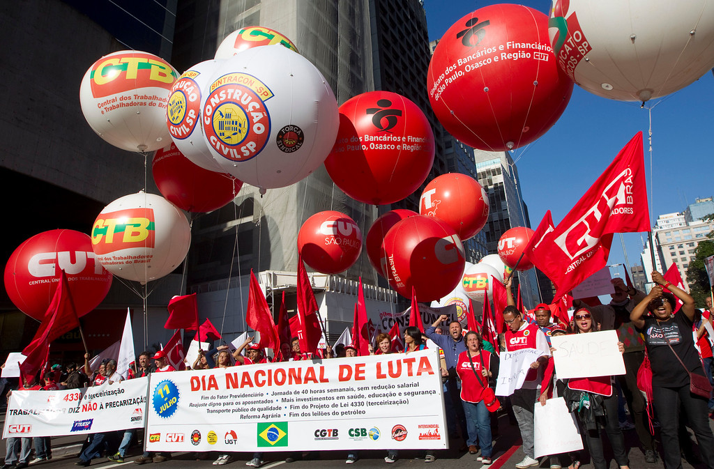 ". Workers march during a strike carrying a sign that reads in Portuguese ""National day of mourning\"" in Sao Paulo, Brazil, Thursday, July 11, 2013. Workers across Brazil walked off their jobs on Thursday in a peaceful nationwide strike demanding better working conditions and improved public services. Metalworkers, transportation and construction workers as well as teachers and civil servants adhered to the \""Day of Struggle\"" organized by Brazil\'s biggest trade union federations. (AP Photo/Andre Penner)"