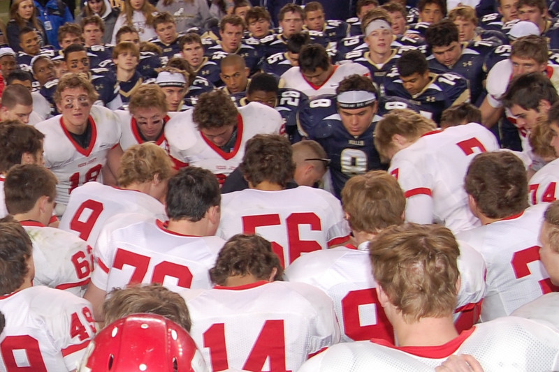 Regis Raiders and Mullen Mustangs surrond Coach Mark Nolan, as they join together in saying The Lord's Prayer after the game.  God bless you all!