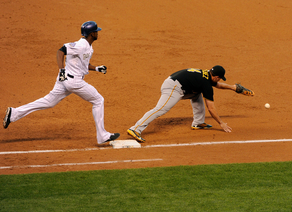 . DENVER, CO. - AUGUST 09: Rockies batter Dexter Fowler was safe at first and advanced to second on a bad throw from Pirates shortstop Jordy Mercer in the second inning. The Colorado Rockies hosted the Pittsburgh Pirates Friday night, August 9, 2013. Photo By Karl Gehring/The Denver Post