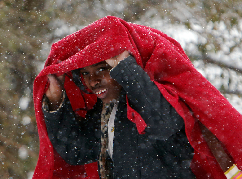 . Maya Tilley covers her head from the blowing snow as she  walks home from school in Childersburg, Ala. Tuesday Jan. 28, 2014. A fast-moving, unexpectedly severe winter storm blanketed much of Alabama with a treacherous layer of frozen precipitation Tuesday.  (AP Photo/Hal Yeager)